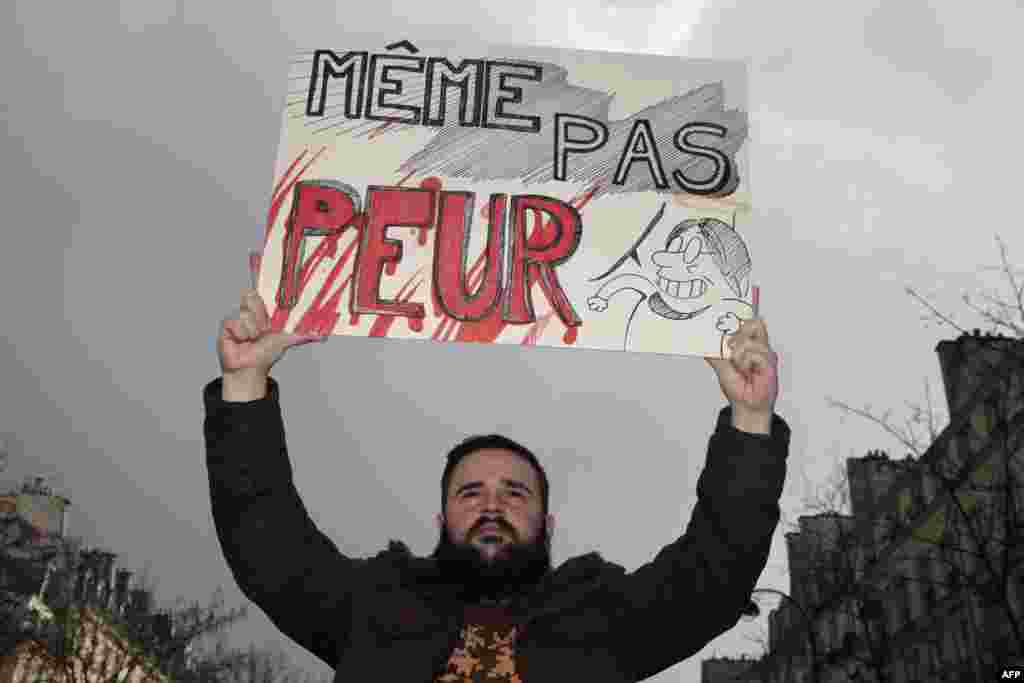 "A man holds a sign that reads ""Not even scared"" at the start of the rally in Paris."