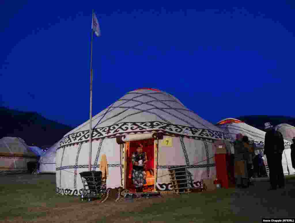 A woman leaves her yurt with a pile of dishes as the games' attendees settle in for the night in the chilly mountain venue.