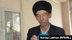 Тусип Айнагул, переселенец из Китая, с удостоверениями оралмана в руках. Иллюстративное фото.