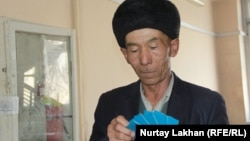 Репатриант из Китая показывает полученные на членов семьи новые документы. Алматы, 25 января 2019 года.
