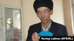 Тусип Айнагул, переселенец из Китая, показывает удостоверения оралмана с истекшим сроком действия. Алматы, 25 января 2019 года.