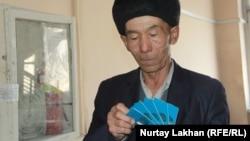 Мужчина с удостоверениями оралманов в руках. Иллюстративное фото.