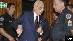 Бывший президент Аргентины Хорхе Рафаэль Видела разговаривает с полицейским перед судом. Декабрь 2010 года.