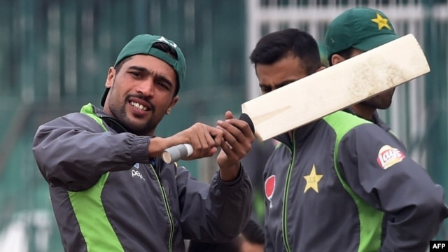 Pakistani cricketer Mohammad Amir (left) takes part in a team practice session in Lahore on January 6.