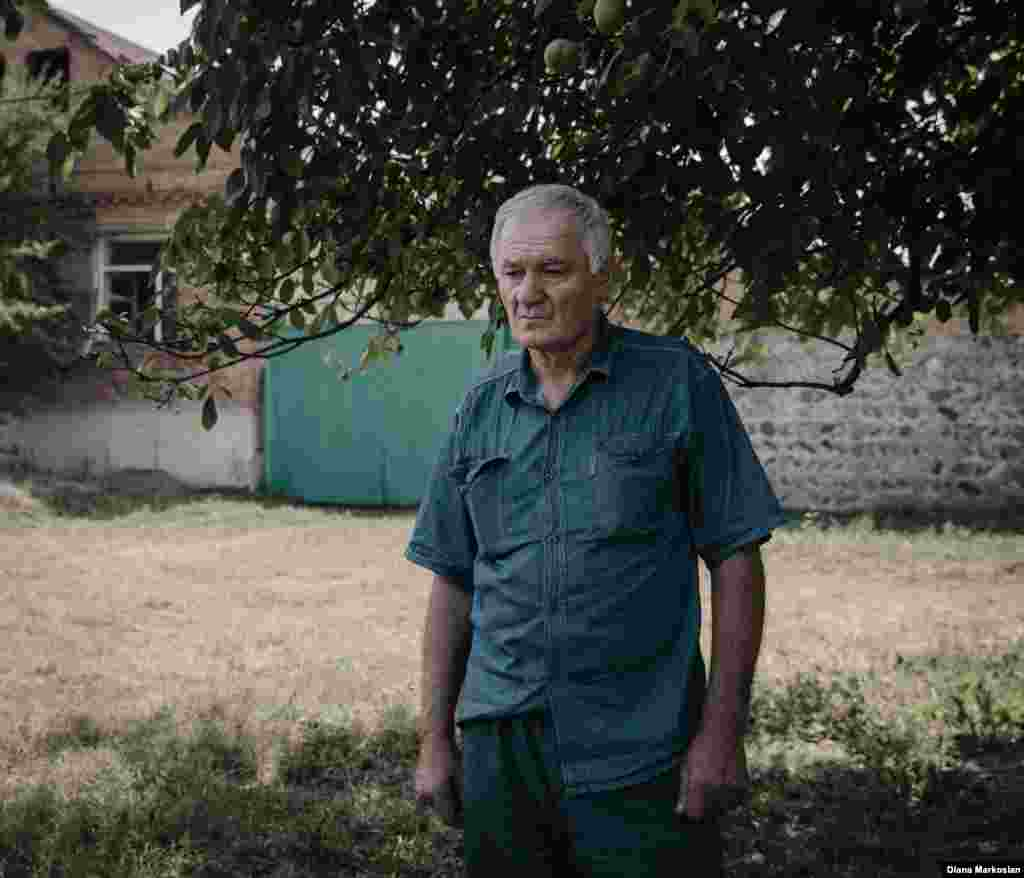 """""""I feel like she is still with us,"""" says Ruslan Kokov, 63. Ruslan was at the market when Oksana walked across the road to school, never to return. On her birthday, Ruslan and his son, Uruzmag, 27, always lay a place for her at dinner. They eat the foods she liked: melon, persimmons, blood oranges. Ruslan is pictured here standing in front of his house on Komintern Street. School No. 1 is clearly visible from his front room. Russian special forces were staked out there during the siege; during the final gun battle, bullets shattered his two front window panes. Ten years later, Ruslan hasn't gotten around to fixing them. """"When I come across something that reminds me of the tragedy, it just upsets me unnecessarily,"""" he says."""
