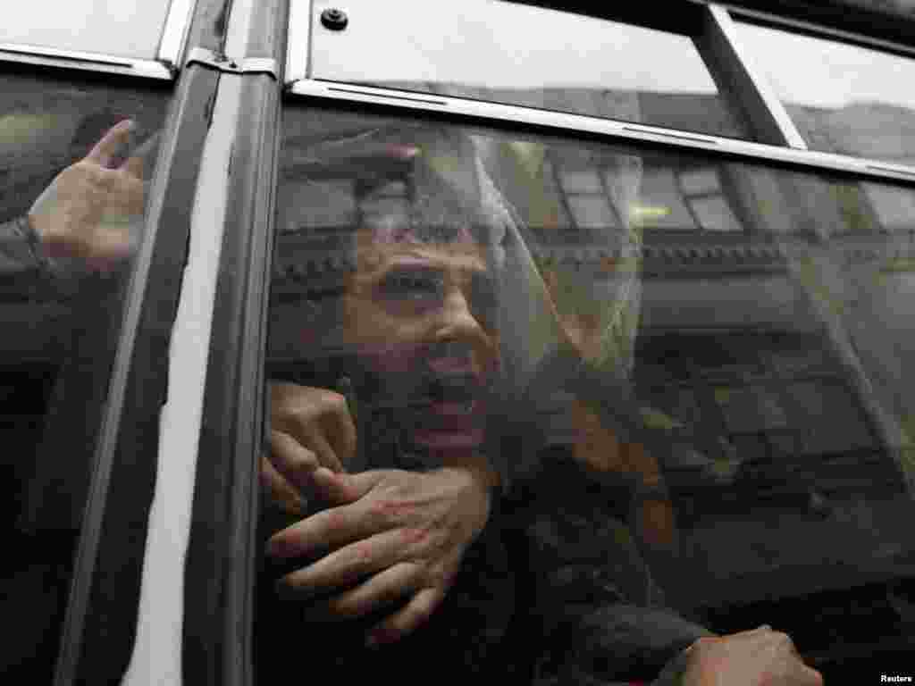 A detained opposition activist shouts in a police van during a protest outside the Election Commission headquarters in Moscow. (REUTERS/Denis Sinyakov)