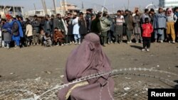 FILE: An internally displaced Afghan woman waits to receive assistance donated by a nongovernmental organization in Kabul.