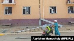 Женщина с ребенком у многоэтажного дома, поврежденного в результате взрывов боеприпасов на военном складе. Арысь, 28 июня 2019 года.