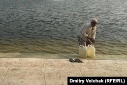 Паломник набирает святую воду из пруда возле мавзолея Хана Джахана Али