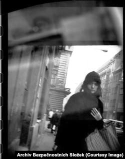 Молодая женщина кутается в пальто, проходя мимо агента со скрытой камерой в центре Праги