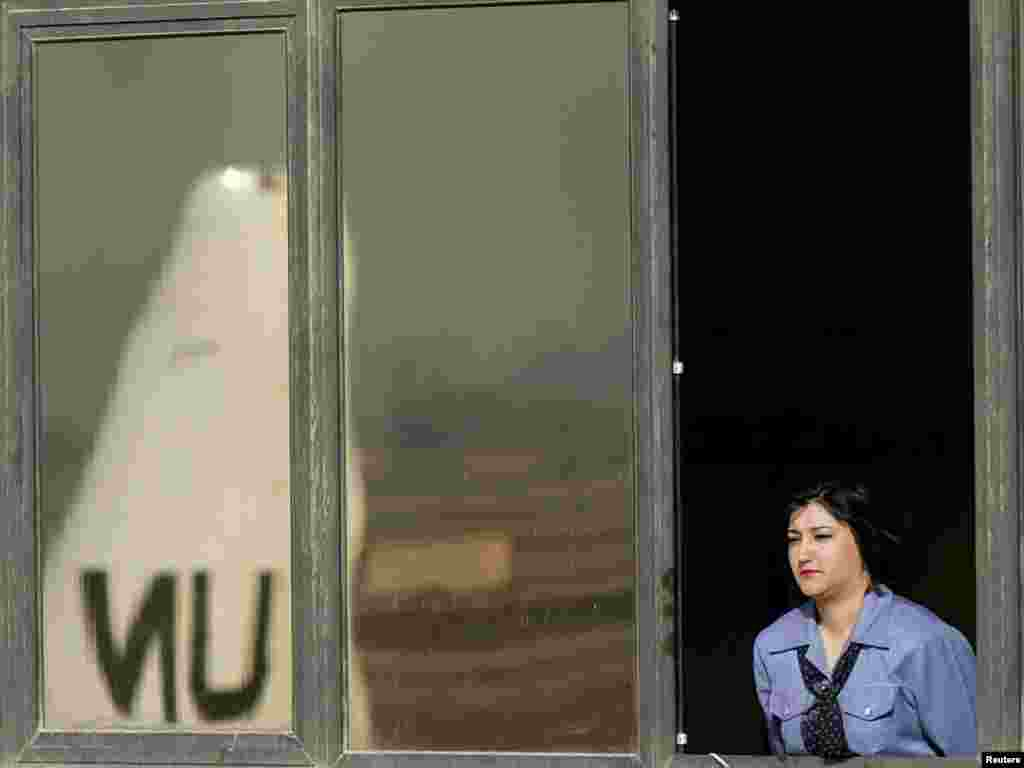 An Iraqi woman watches U.N. weapons inspectors leave Saddam airport in Baghdad March 18, 2003. Weapons inspectors left Iraq by plane on Tuesday after the United Nations told them to cut short their hunt for hidden weapons of mass destruction ahead of a likely U.S.-led invasion. REUTERS/Goran Tomasevic