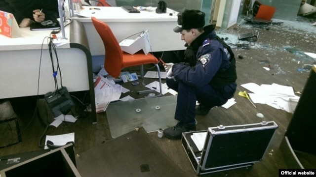 Police inspect the damaged Alfa Bank in Kyiv after the attack.