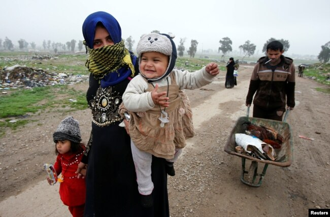 Displaced Iraqis from different areas in Mosul flee their homes after clashes broke out as Iraqi forces battle with Islamic State militants in the city on March 17.