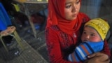 A Uyghur woman holds her baby at a market in Hotan in China's western Xinjiang region. (file photo)