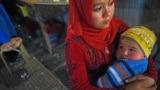 Женщина-уйгурка с ребенком на руках на рынке в Хотане, городе в Синьцзяне.