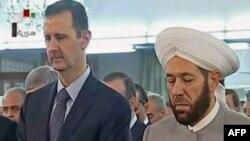 Сирия президенті Башар Асад (сол жақта) елдің бас мүфтиі Ахмед Хассунмен бірге намаз оқып тұр. Дамаск, 8 тамыз 2013 жыл.