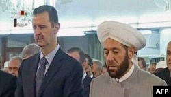 A TV screenshot apparently shows Syrian President Bashar al-Assad (left) attending morning prayers in Damascus on August 8.