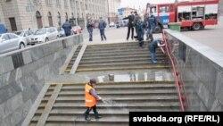 Супрацоўніца камунальных службаў прыбірае падзямельны пераход у станцыю мэтро пасьля выбуху