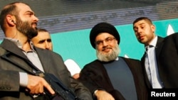 حسن نصرالله (در وسط تصویر) این اتهامها را در یک مصاحبه تلویزیونی بیان کرده است
