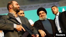 "Hizballah leader Sayyed Hassan Nasrallah (second from right) in Beirut in 2012. Among other things, the State Department report said that ""terrorist groups supported by Iran -- most prominently Hizballah -- continued to threaten U.S. allies and interests."" (file photo)"