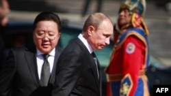 Russian President Vladimir Putin is escorted by Mongolian President Tsakhiagiin Elbegdorj (left) during a welcoming ceremony in Ulan Bator.