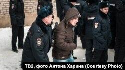 Полицейский и иностранец у миграционного центра в Томске