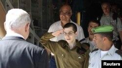 اسراییل: په فلسطین کېد حماس لخوا خوشي شوی اسراییلي عسکر ته د اسراییلو لومړی وزیر بین یامین نتن یاهو هرکلي ته ولاړ دی او دی سلامي ورته کوي.۱۸ اکتوبر ۲۰۱۱ م کال