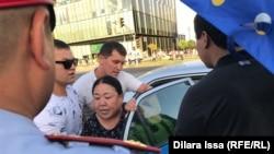 Люди в гражданской одежде усаживают в автомобиль полиции задержанную женщину. Шымкент, 6 июля 2019 года.