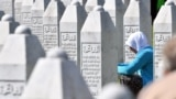 BOSNIA-HERZEGOVINA -- Bosnian Muslim woman, survivor of Srebrenica 1995 massacre, prays near graves of her relatives, at the memorial cemetery in Potocari, near Eastern-Bosnian town of Srebrenica, on July 11, 2019.