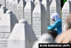 A Bosnian Muslim woman, a survivor of the 1995 Srebrenica massacre, prays near the graves of her relatives at the memorial cemetery in Potocari, near Srebrenica, on July 11.