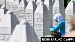 A woman prays near the graves of victims of the Srebrenica massacre in Bosnia-Herzegovina. (file photo)