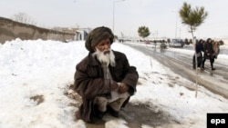 An Afghan man sits on a snow-covered road after heavy snowfall on the outskirst of Kabul