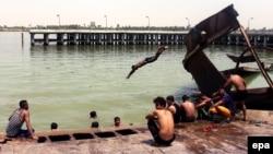 Iraqis swim near Basra in an effort to beat the searing summer heat on August 3.