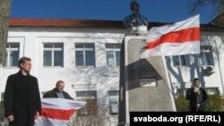 Юры Глебік побач з помнікам Кастуся Каліноўскага трымае бел-чырвона-белы сьцяг у руках