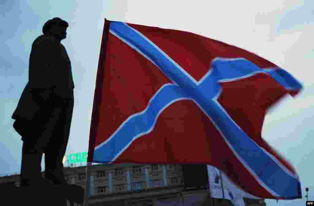 "The ""New Russia"" (Novorossia) flag flies next to the statue of Soviet founder Vladimir Lenin on Lenin Square in the eastern Ukrainian city of Donetsk. (AFP/Dominique Faget)"