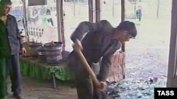 Рабочий убирает мусор и осколки после взрыва бомбы. Ташкент, 30 марта 2004 года.