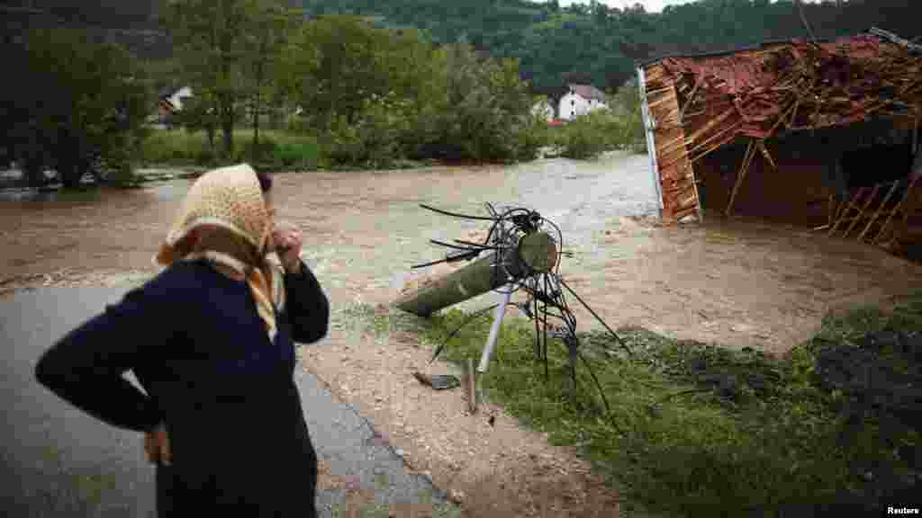 A woman stands near a river and looks at a house that was destroyed during floods in Potocari near Srebrenica, Bosnia-Herzegovina, on May 25. (Reuters/Dado Ruvic)
