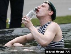 مردی در روسیه روز نگهبان مرزبانی را در حال نوشیدن ودکا در چشمه ای در مسکو جشن می گیرد.  (عکس بایگانی)
