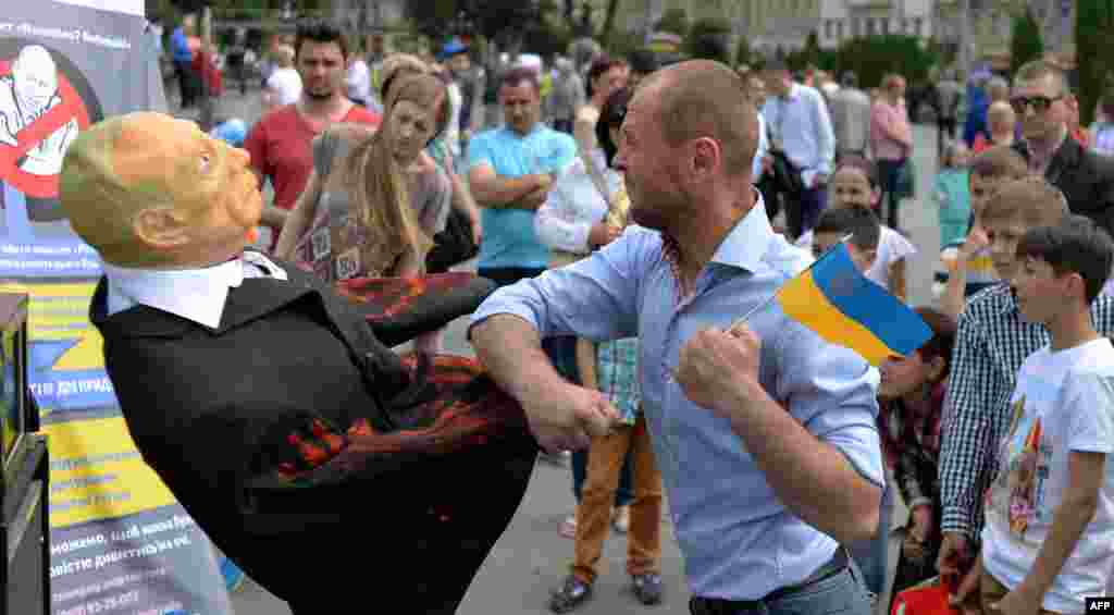 A man punches an effigy of Russian President Vladimir Putin on a street in the western Ukrainian city of Lviv. (AFP/Yuriy Dyachyshyn)