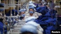 Кэсон өнөр жай зонасындагы түштүк кореялык фирманын тигүү цехинде иштеген Түндүк кореялыктар. 19-декабрь, 2013