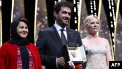 Iranian actor Shahab Hosseini (center) poses with Cannes jury members Iranian producer Katayoon Shahabi (left) and American actress Kirsten Dunst after being gvien the Best Actor prize during the closing ceremony of the 69th Cannes Film Festival.