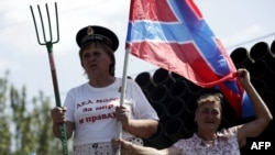 A woman rides on the back of a truck holding a pitchfork and a flag of Novorossia last August in Donetsk.