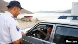 Policajac provjerava pasoš na granici u Neumu