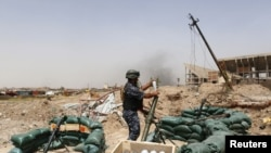 Një pjesëtar i forcave të sigurisë së Irakut duke u përgatitur për të sulmuar me predhë kundër pozicioneve të IS-it në Mosul