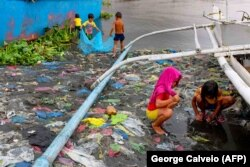 Дети в трущобах Манилы, столицы Филиппин, ловят маленьких рыбок для еды. Осень 2020 года