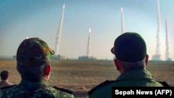 A Forradalmi Gárda parancsnoka figyeli a rakéták kilövését egy meg nem nevezett helyszínen tartott hadgyakorlaton Iránban 2021. január 15-én.