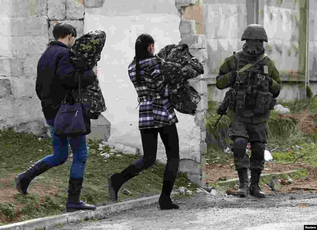 Two women, believed to be Ukrainian servicewomen, carry their uniforms as they walk past an armed man, believed to be a Russian serviceman, while leaving a military base in Perevalnoye, near Simferopol in Crimea on March 19. (Reuters/Shamil Zhumatov)