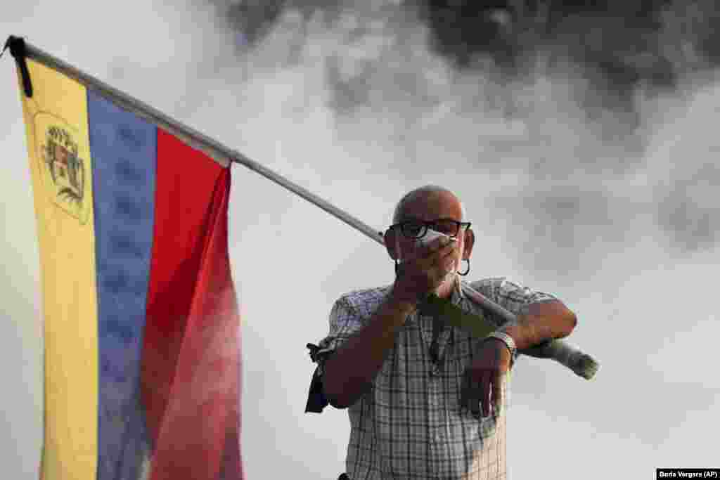 An anti-government protester carrying a Venezuelan flag covers his face amid tear gas fired by soldiers loyal to President Maduro during an attempted military uprising in Caracas on April 30. (AP/Boris Vergara)