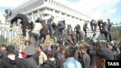 Люди пытаются перелезть через ограду здания парламента. Бишкек, 3 октября 2012 года.