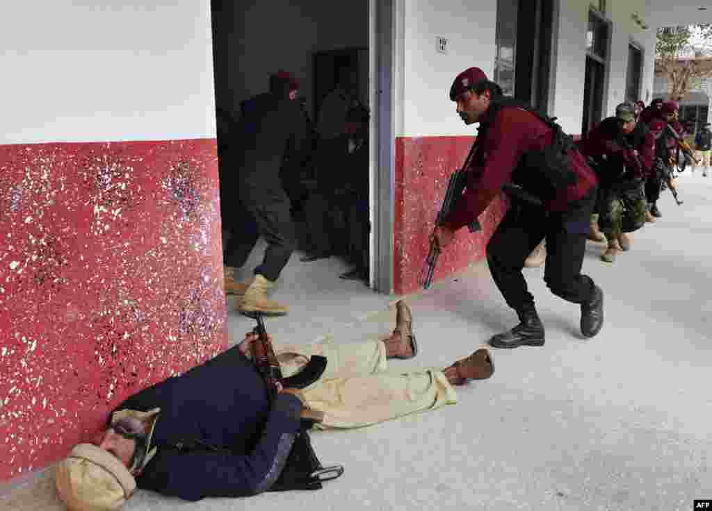 Members of Pakistan's Elite Police Force take part in a drill to fight against militants at a school in Peshawar on January 28.  (AFP/A. Majeed)